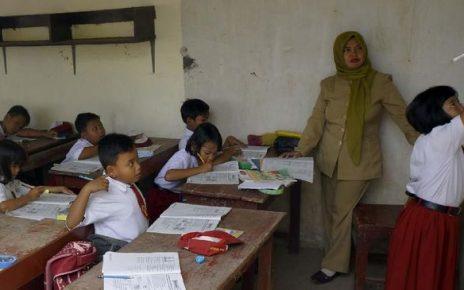 MENGAJAR. Guru sedang mengajar sebelum masa pandemi covid. (foto: cnnindonesia)