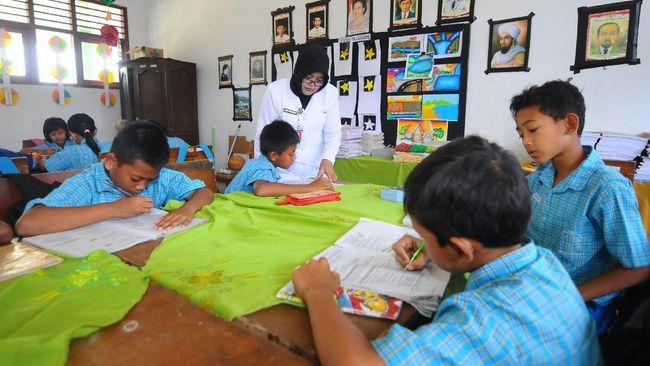 MENGAJAR. Guru saat memberi pembelajaran sebelum pandemi. (foto: cnnindonesia.com)