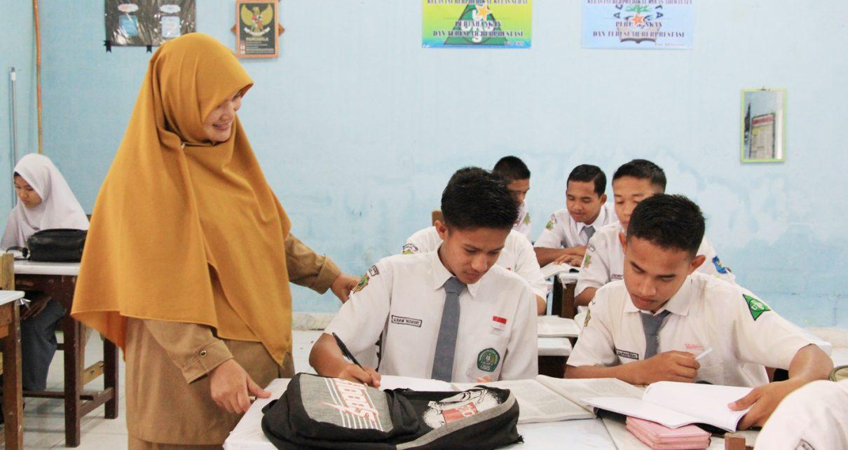 MENGAJAR. Guru sedang memberi penjelasan ke siswa. (foto: suhanews.co.id)